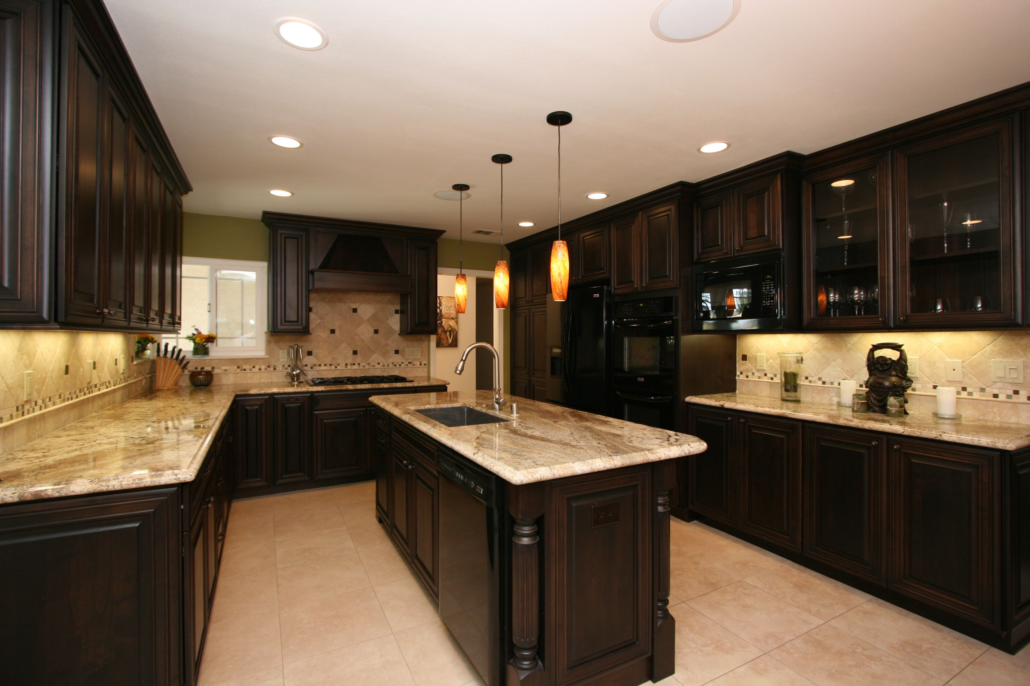 Open shelving balances the use of black cabinetry in this stunning kitchen.  Marbled black granite