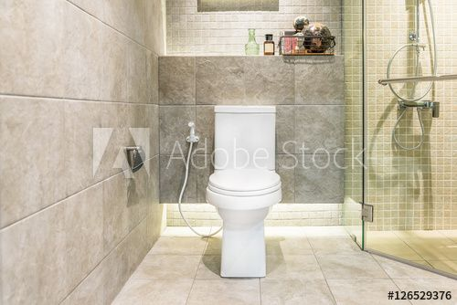 Photo of White toilet bowl in modern bathroom at hotel. Interior of toile