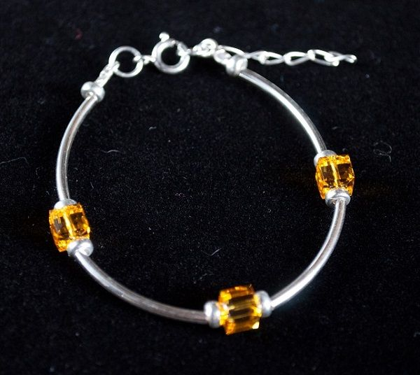 Sterling silver bracelet with tube beads, donut beads and Swarovski elements in sunflower