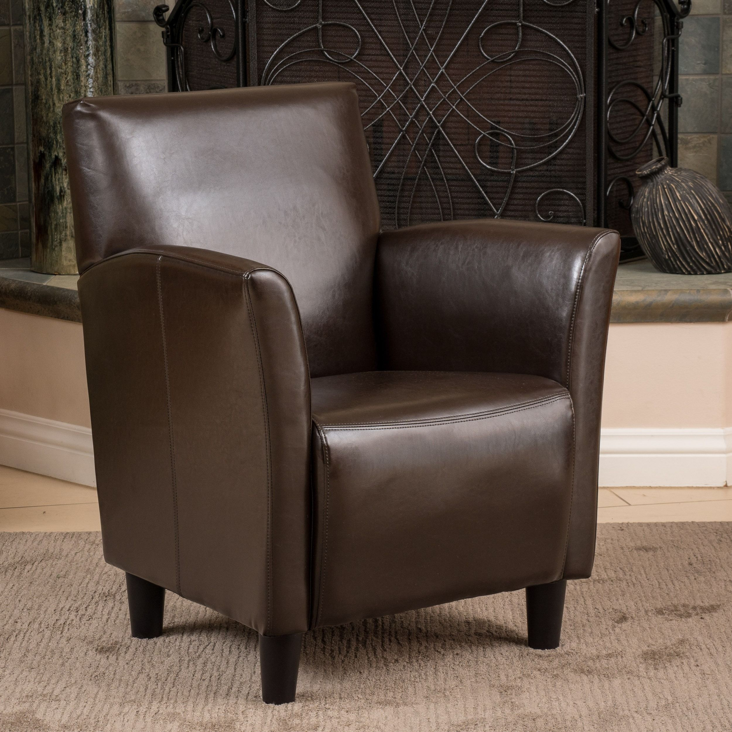 Add style to your home with this sophisticated bonded leather club chair from Francisco. This chair features beautiful brown leather upholstery and dark-finish legs. It is constructed of solid wood for added stability and durability.