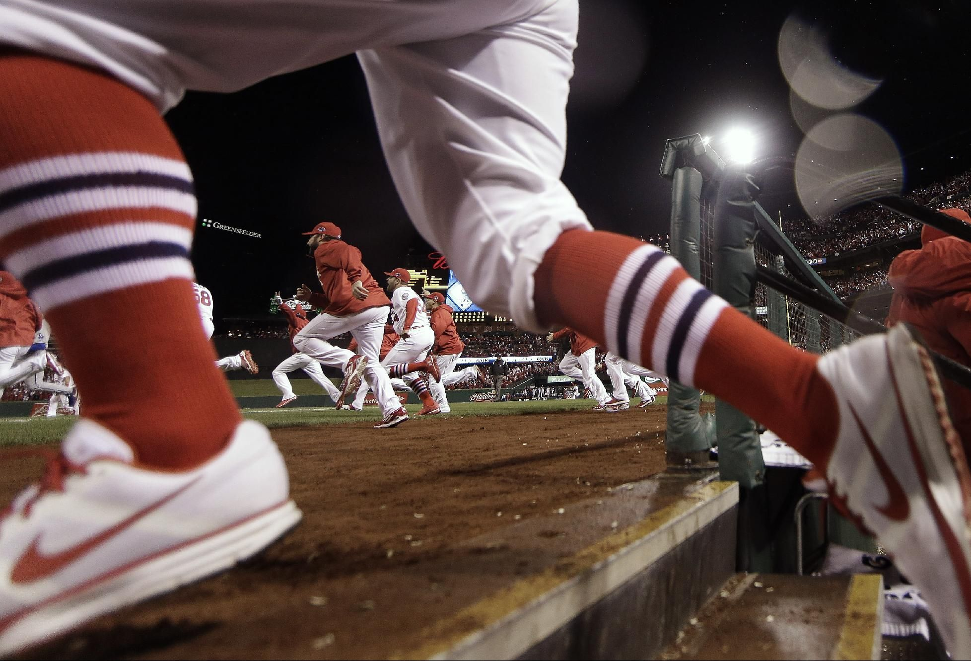 The St. Louis Cardinals run out of the dugout after Game 6