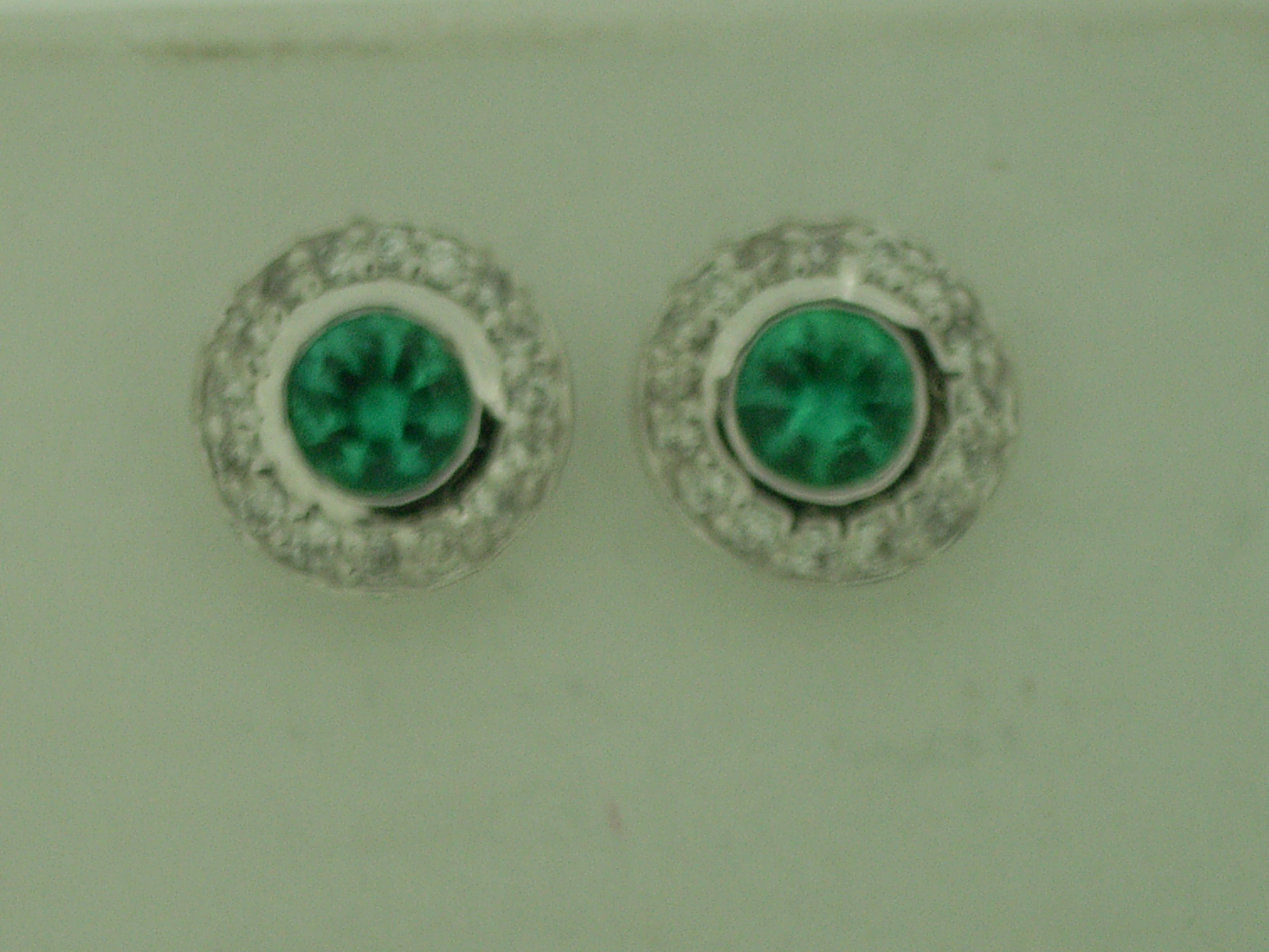Halo style emerald and diamond earrings set in white gold earring
