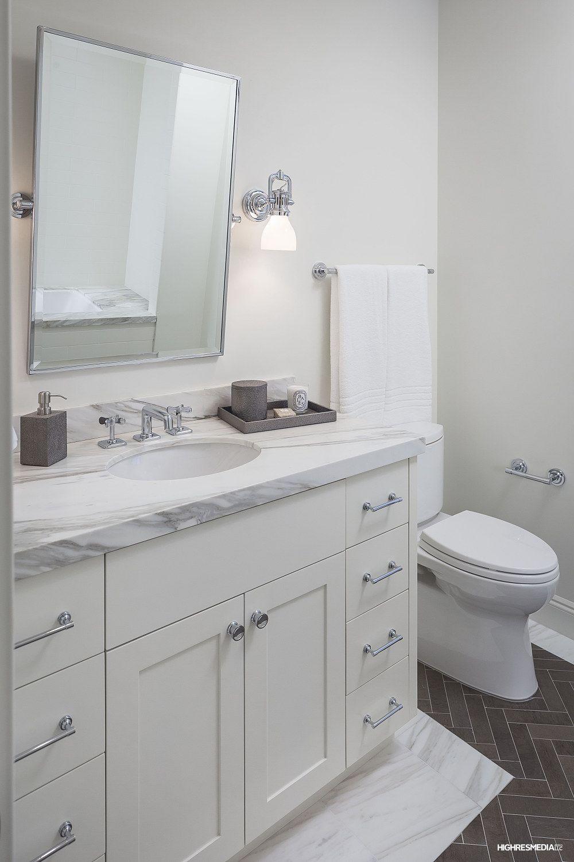 Limestone Herringbone Floors within Calacatta Border, Custom Millwork,  Waterworks Plumbing Fixtures at Guest Bath.