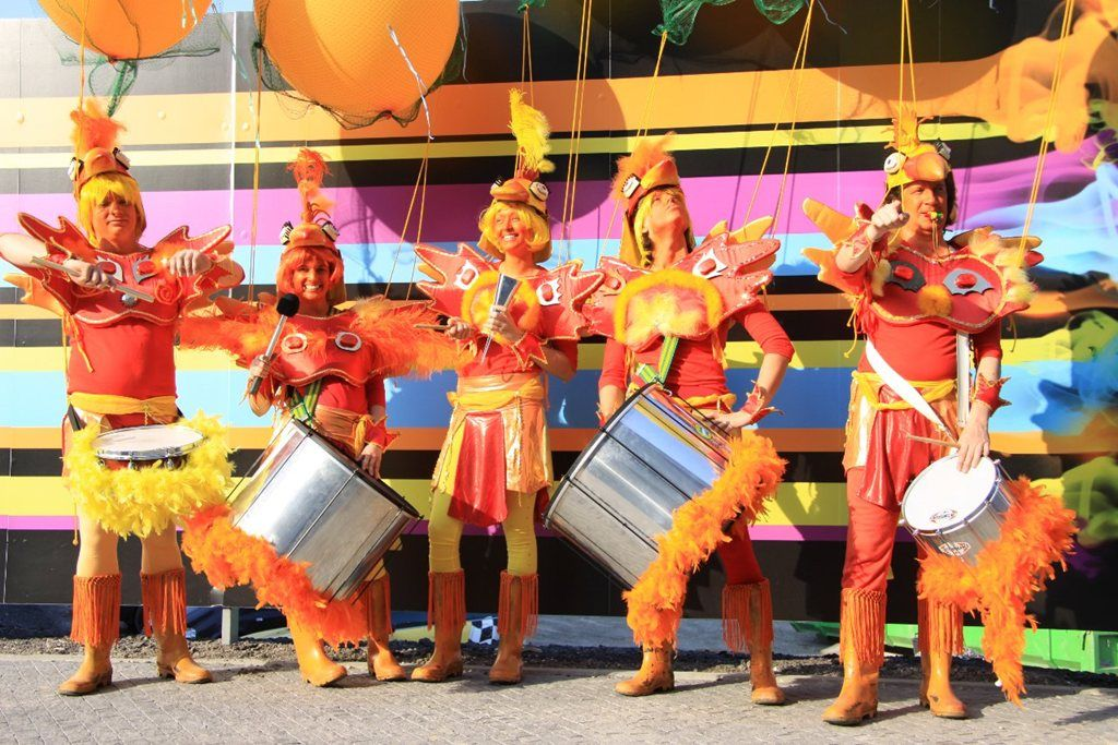 The Chicken Drummers - These Chicken Drummers parade through corporate events, private parties, fun days, festivals, parades, theme parks and carnivals in their amazing and colourful costumes. Experience the high energy grooves and funky moves of this orange explosion!