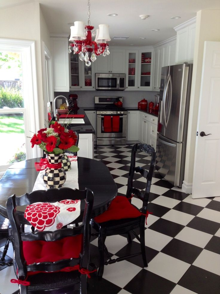 Fun black and white kitchen with red accents and a checkerboard floor.