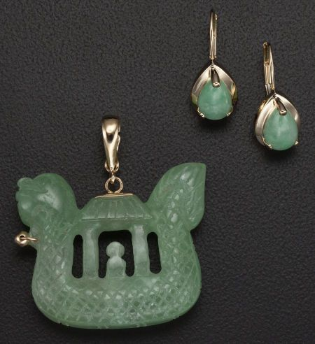 A carved jadeite jade jewelry set, featuring a pair of jade cabochon earrings set in gold and a carved pendant with gold fixtures.
