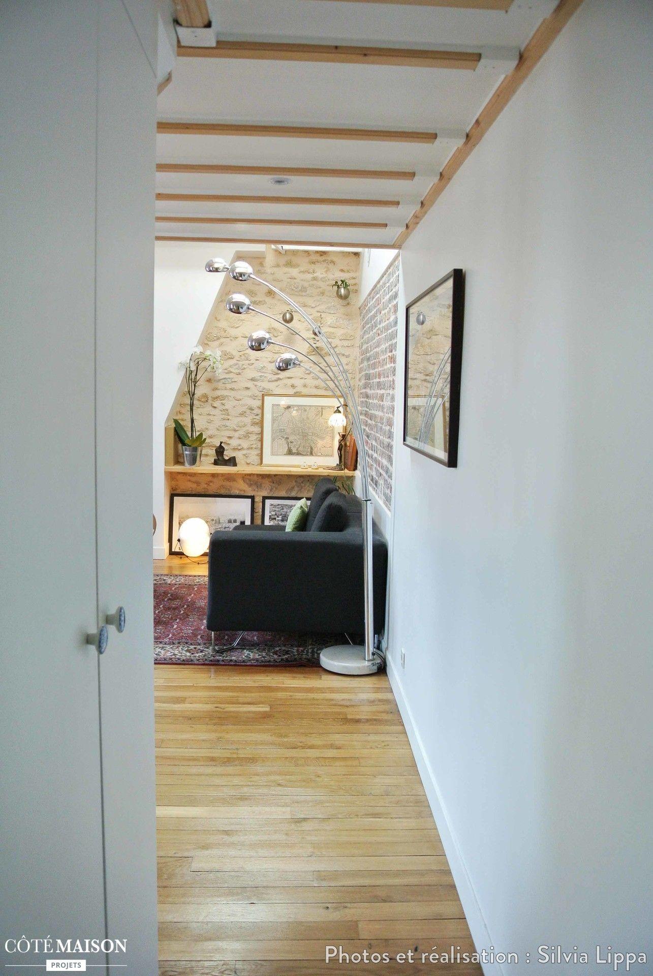 Les poutres apparantes et l'univers du salon au bout suffit pour aménagé ce couloir.