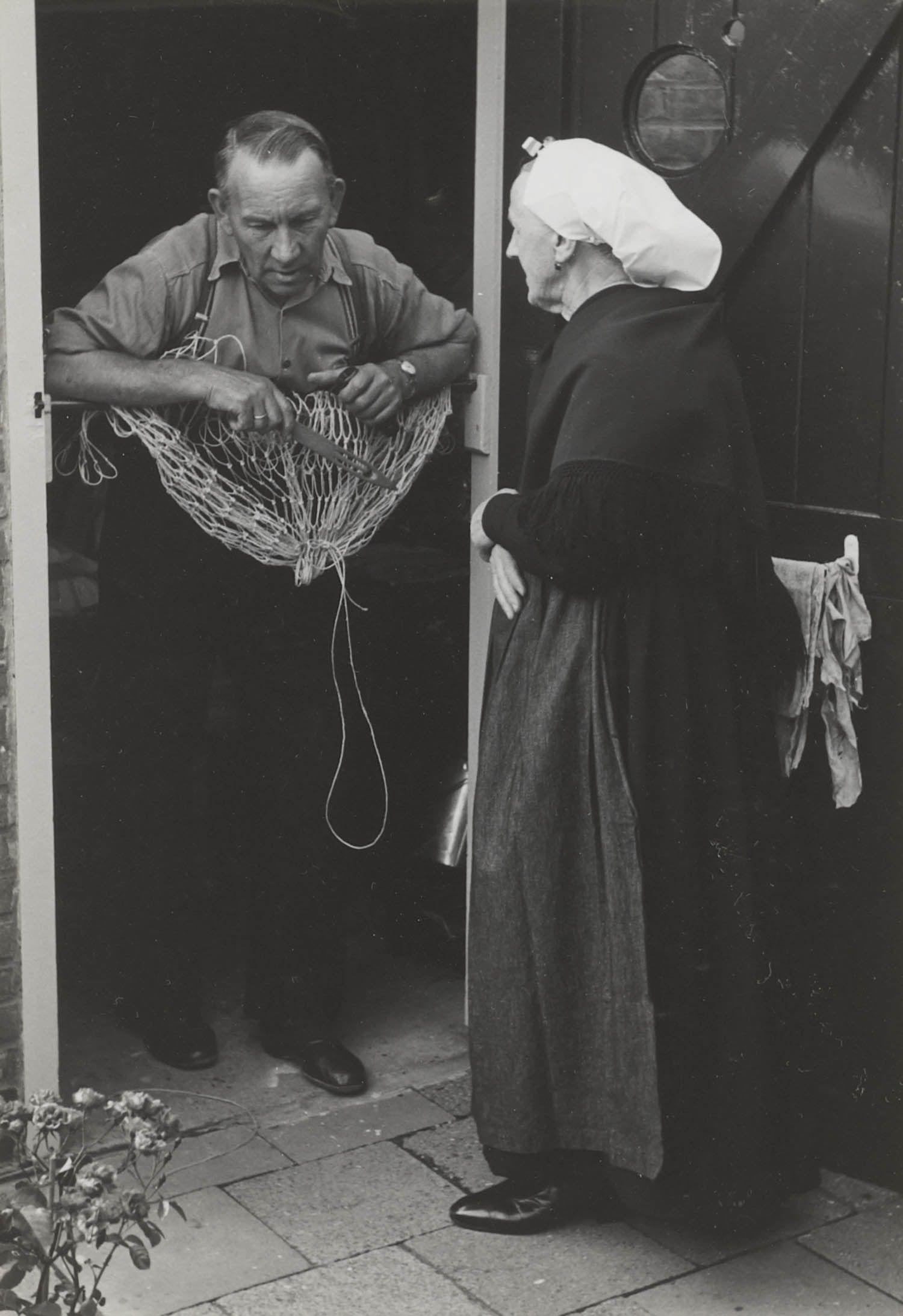 Man en vrouw in Scheveningse dracht, 1953 de man is bezig met netten boeten (met houten boetnaald). De vrouw draagt een ouderwetse muts met 'vierkante klappen'. Ze is in de rouw. Onder de muts draagt ze een zilveren oorijzer met 'stukken'. Ze is gekleed in haar opknappersgoed: zwarte schouderdoek, zwart jak, zwarte rok en een donkergrijs schort van keizers- of verpleegsterslinnen. #ZuidHolland #Scheveningen