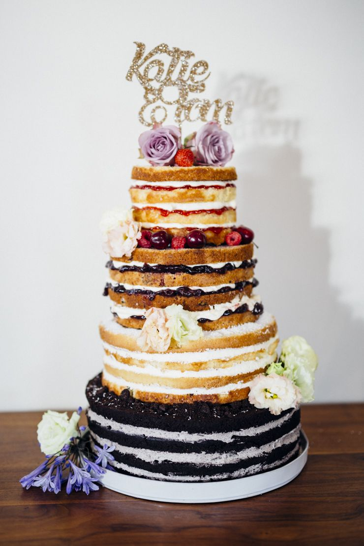 naked rustic wedding cake with different flavor cakes and fillings decorated with flowers image