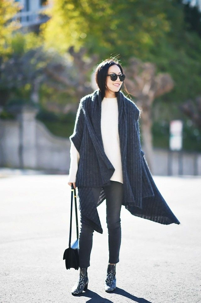 9 to 5 Chic wears a neutral sweater, skinny jeans, snake-print boots, a long sweater, and black accessories