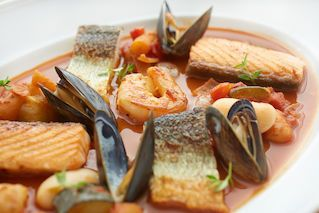 Bouillabaisse: a traditional French shelfish soup, which contains salmon, whitefish, king prawn tails, blue mussels & Provencal vegetable bake, served with french fries and aioli.