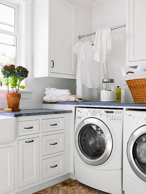 white laundry room. blue soapstone countertops, brick floor, extention rod for hanging clothes
