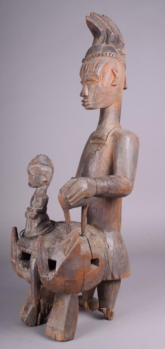 Lot 334 - A Urhobo shrine figure Iphri Nigeria standing with a triple crested coiffure and scarifications to