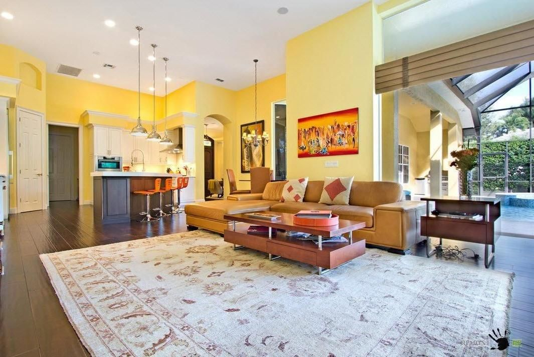 Mild yellow wall color decorates an open living space with brown ...