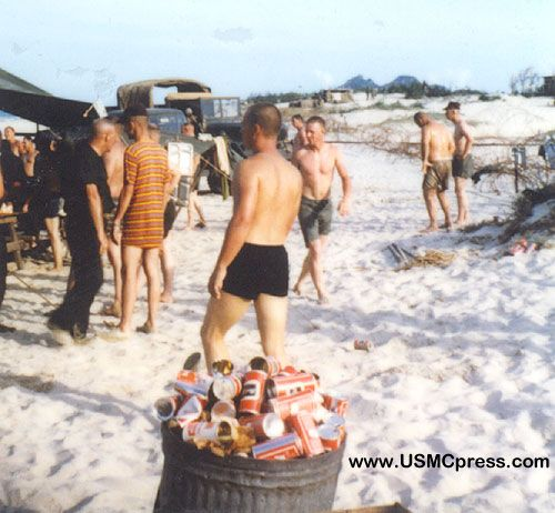 Beer and steak party! On the beach at Marble Mountain, pilots and aircrewmen not on the flight schedule take a much-needed break. The steaks aren't visible, but the trash barrel is full of Carling Black Label cans. Note the concertina in the right background.