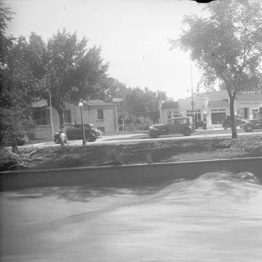 "Cherry Creek flood, Speer Boulevard View of the Cherry Creek flood in Denver, Colorado after the Castlewood Canyon Dam break; shows torrents of water, automobiles on Speer Boulevard, and a gas station with tile roof and sign: ""Standard Oil Company."" Date	1933 August 3:: Western History"