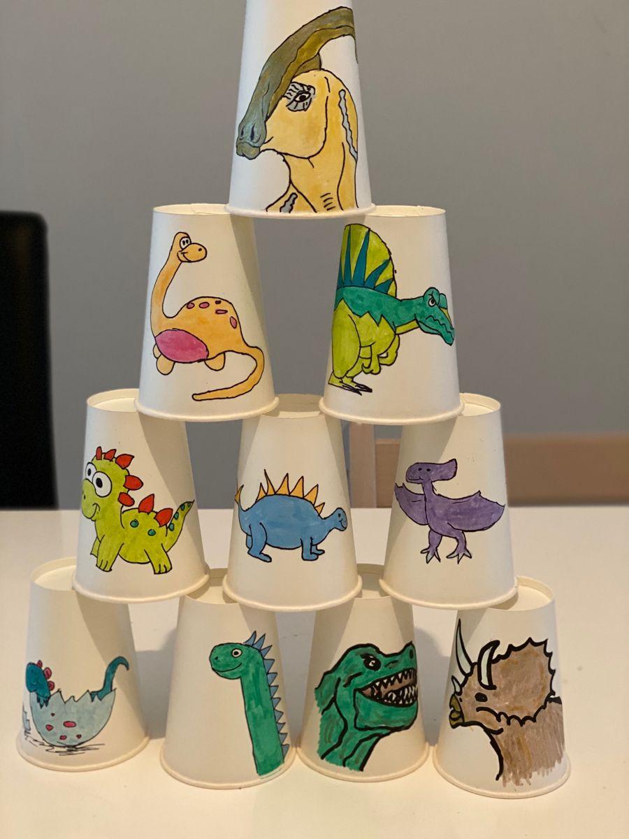 Zum 5. Kindergeburtstag gibt es eine Dino-Party. Da darf das klassische Dosenwerfen nicht fehlen. Die Dosen sind Pappbecher mit tollen Dinomotiven.