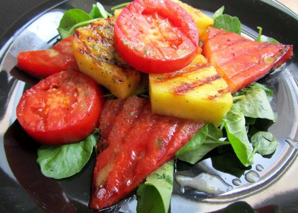 Grilled Pineapple Watermelon Salad: This delightful fruit salad uses its lemon basil vinaigrette as a marinade for the usually cool watermelon, pineapples and tomatoes. Crunchy greens provide a hearty bed for these fresh fruit, grilled smoky sweet. #MeatlessMonday #Salad