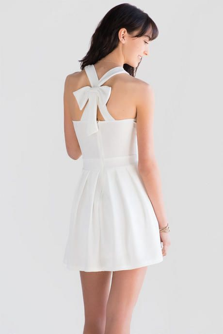 ba2531138ba3 Ava Bow Back Dress features a halter silhouette with a blooming bow in the  back   comes in a choice of white or black. Perfect spring summer date  night ...
