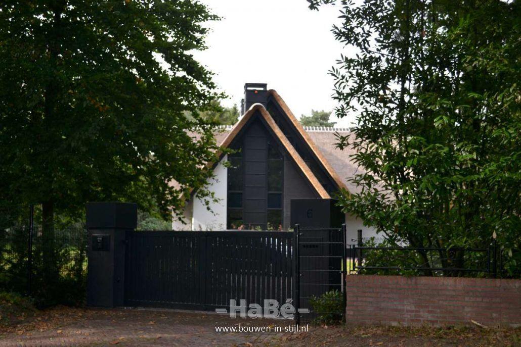 Nieuwbouw moderne villa met rietgedekte kap hekwerk modern