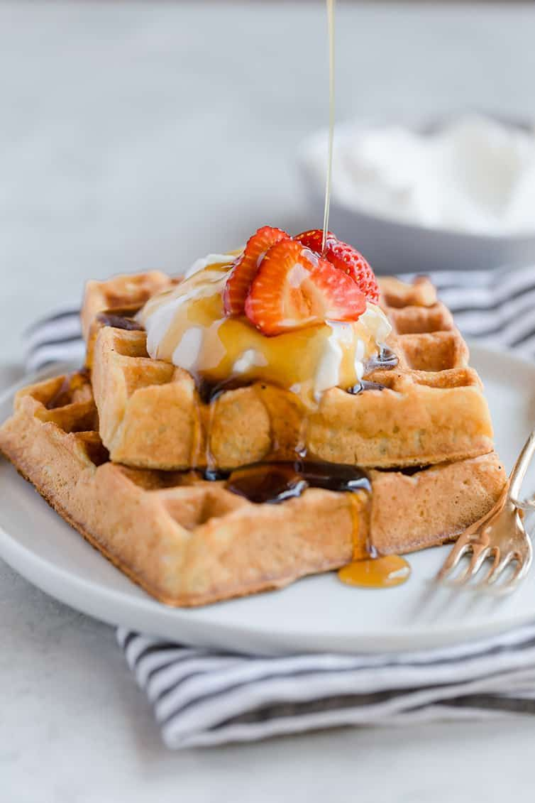 Two Square Waffles Stacked With Whipped Cream And Strawberries On Top Buttermilk Waffles Waffle Recipes Homemade Waffles