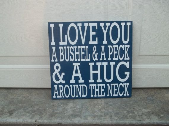This listing is for an approximate 12x12 wood sign. The sign is painted in navy blue and has the saying I love you a Bushel and a Peck, and a Hug