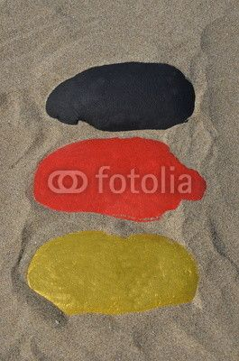 German national flag on three stones over the sand