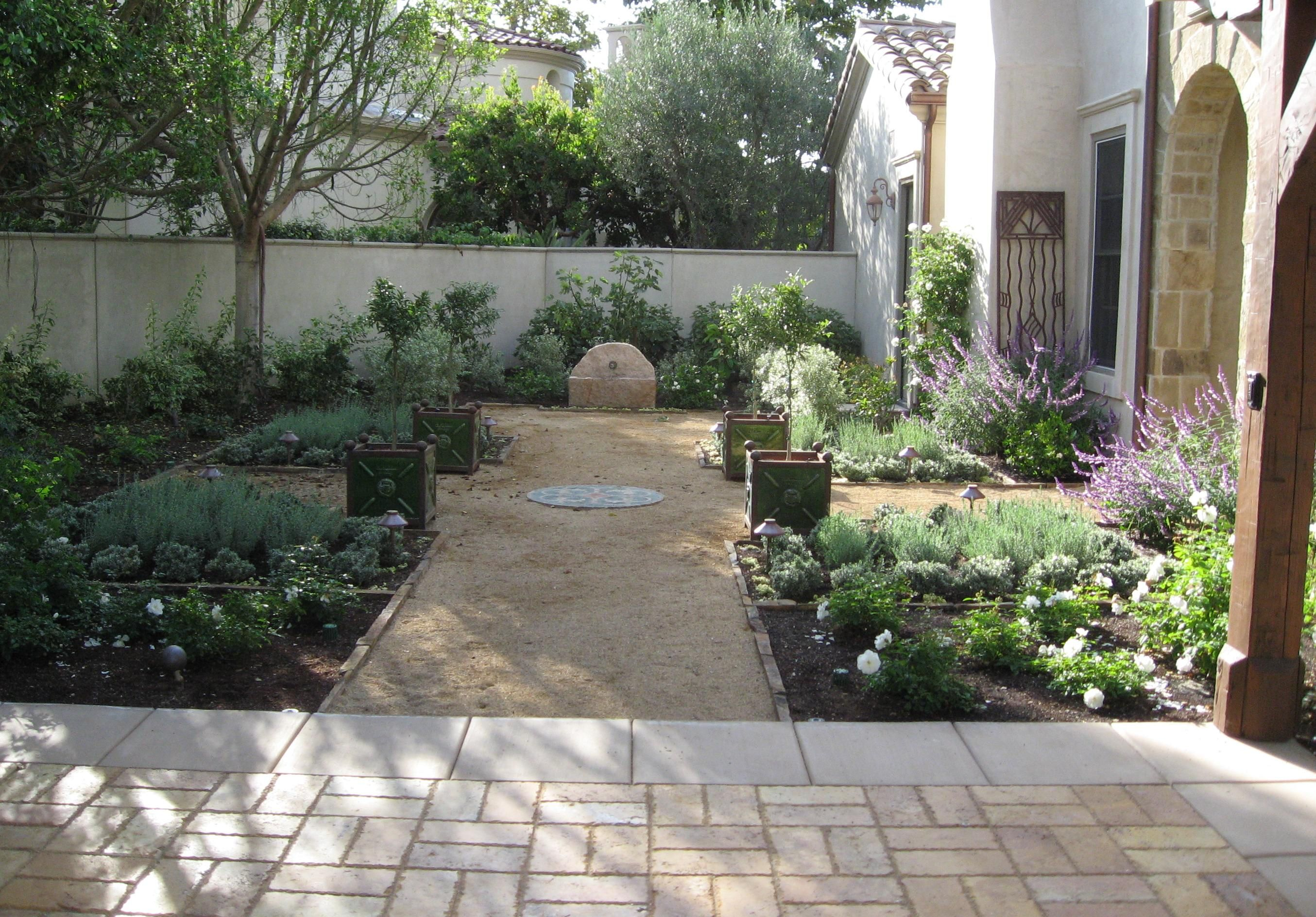 Formal mediterranean garden with small stone fountain for Italian garden design
