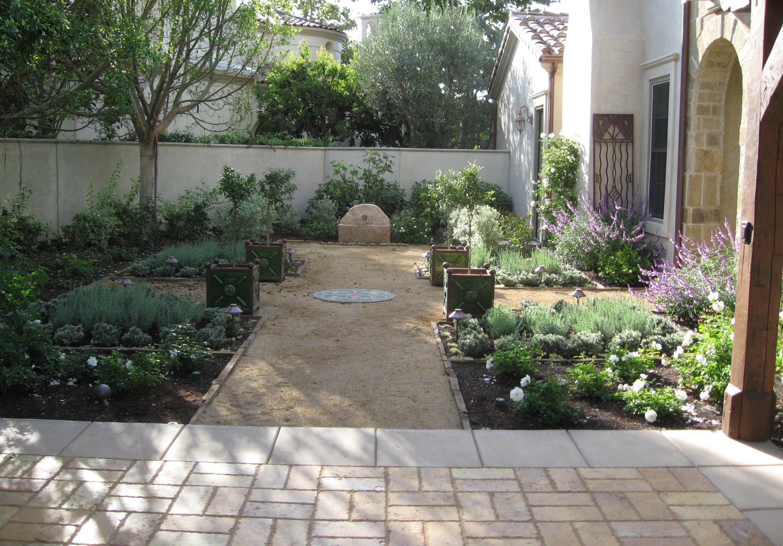 Formal Mediterranean garden with small stone fountain ... on Small Mediterranean Patio Ideas id=71223