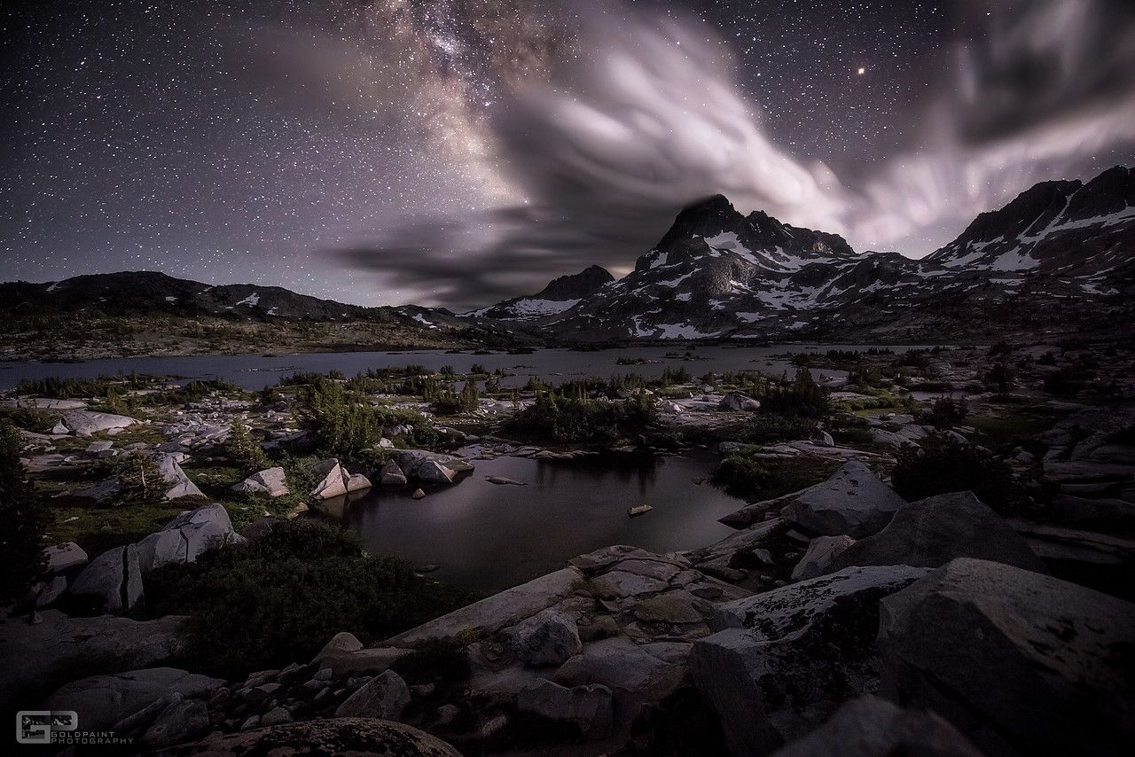 Clouds explode over a mountain peak as the moon sets along the