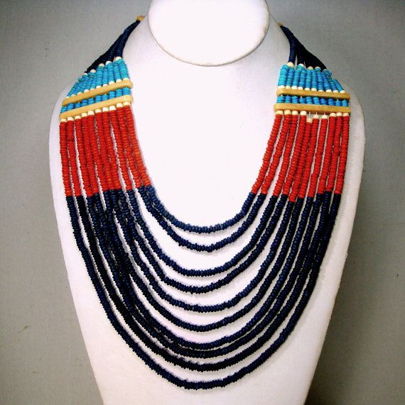 Tribal Multistrand Colorful Ceramic Bead Necklace,10 Strands, 1980s, Blueblack, Red, Turquoise, Purple, Tan, Native American Statement Style Happy Colored CLASSIC BIB necklace of 10 strands ceramic and oxbone divider beads with button and loop catch  This Big colorful Statement necklace is 26 long the longest strand ( 66.04cm ) 19 is the top strand ( 48.26cm )  Immaculate  . I said ceramic , but it might be porcelain beads, when I tap it to my tooth it sounds almost glasslike! gift worthy…