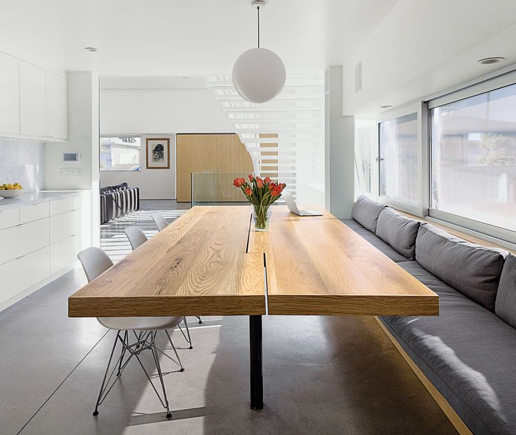 modern kitchen with wood table, concrete floors, and pendant light