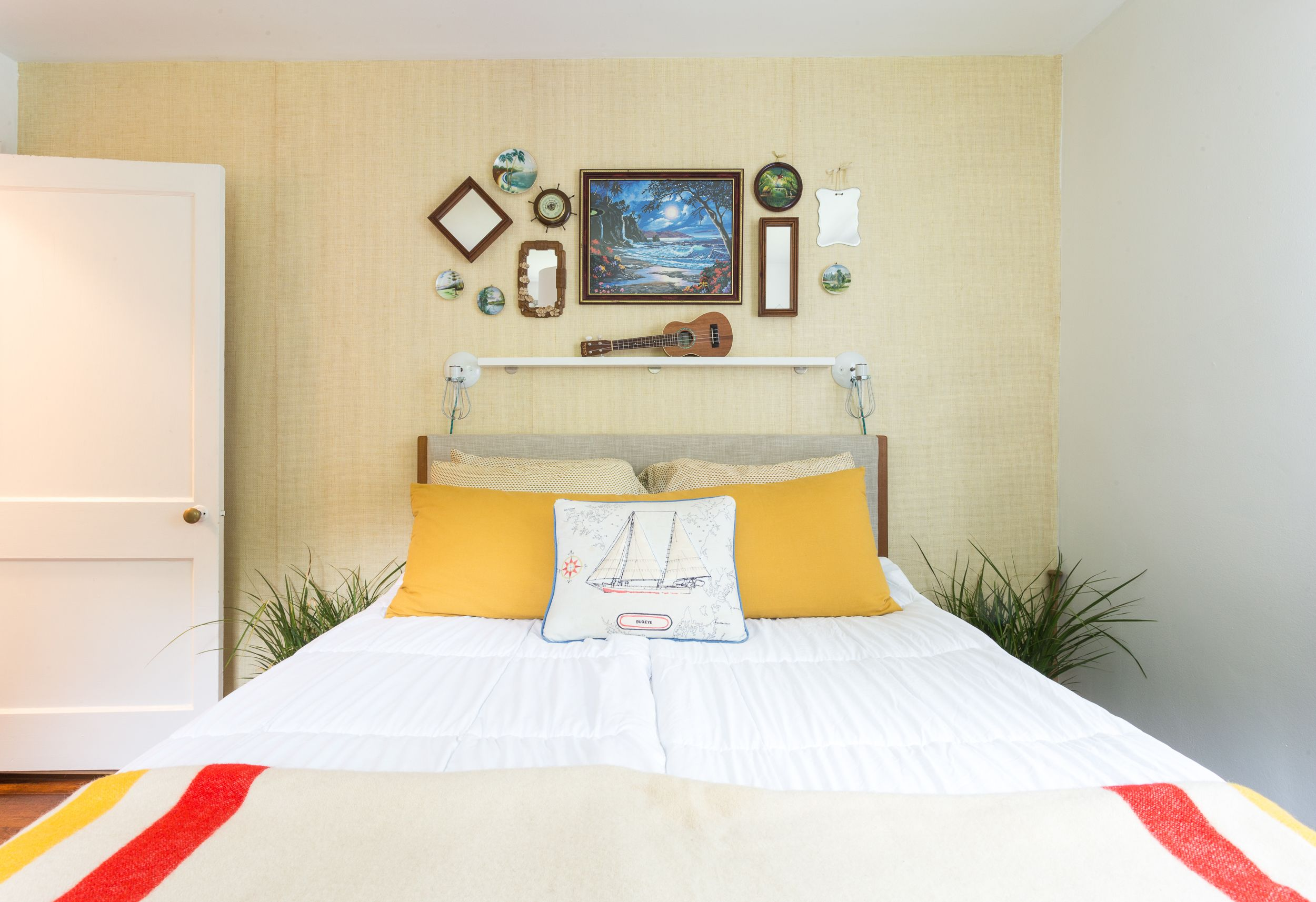 The bed frame is from West Elm and the tropical-themed art is ...