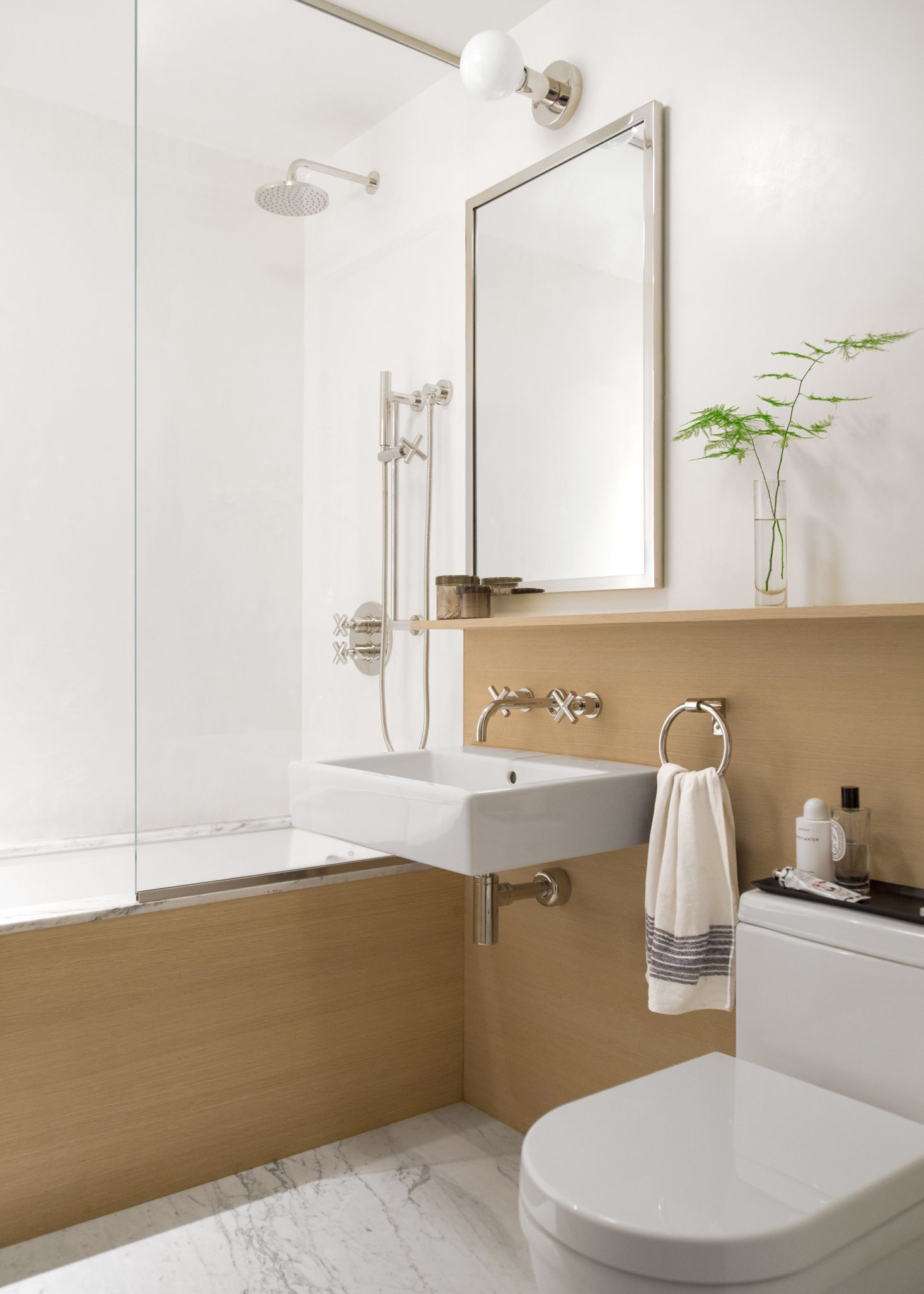 The half wall built in shelf and bathtub surround were constructed from oak The floor is a slab of honed White Gioia—the same material that surrounds the