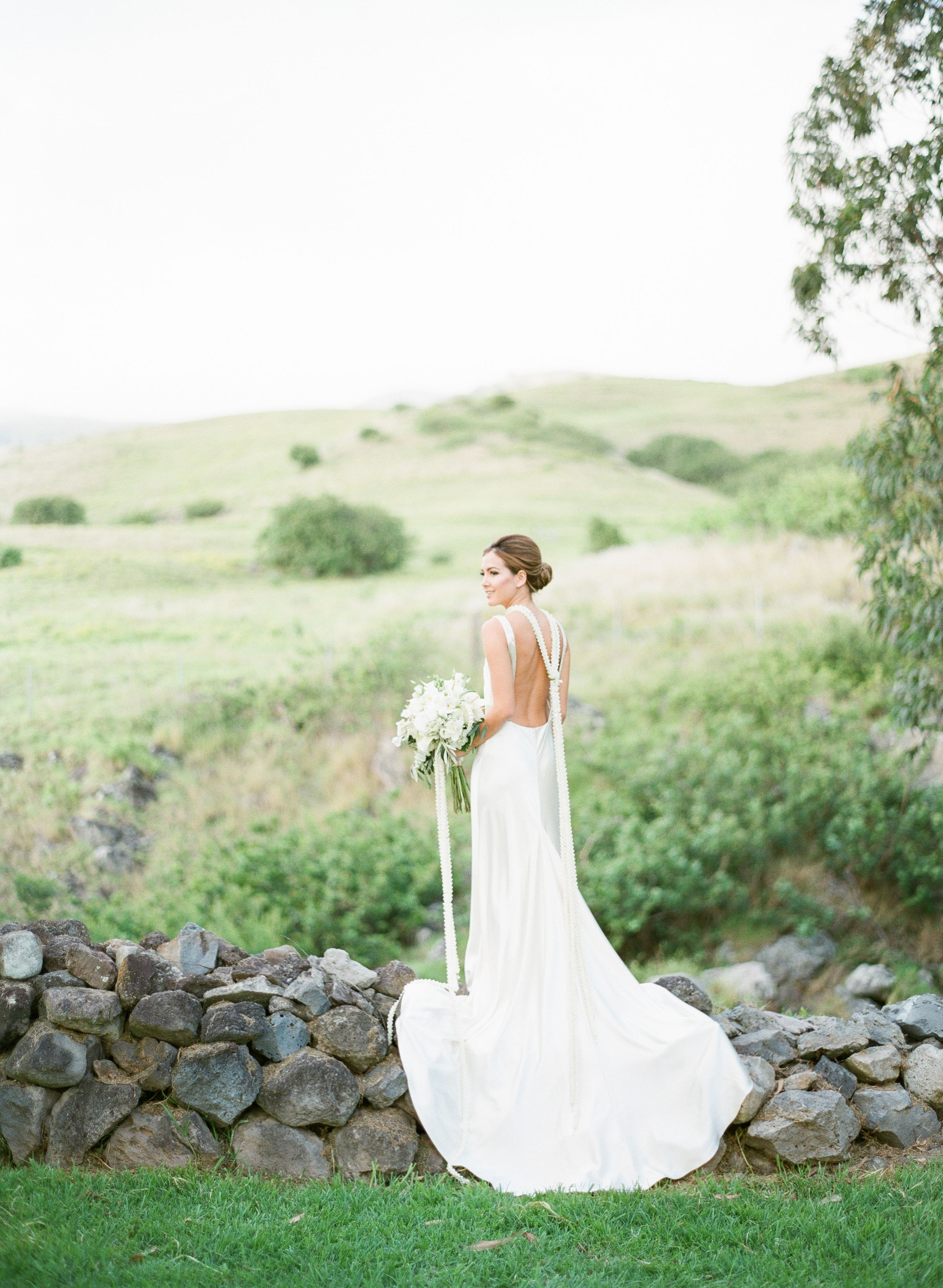 Modern bride draped in a timeless gown and hawaiian flowers