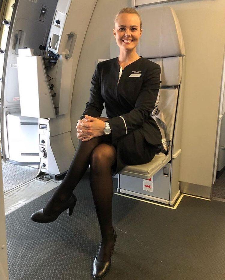 Female Flight Attendant in black dress & black pantyhose
