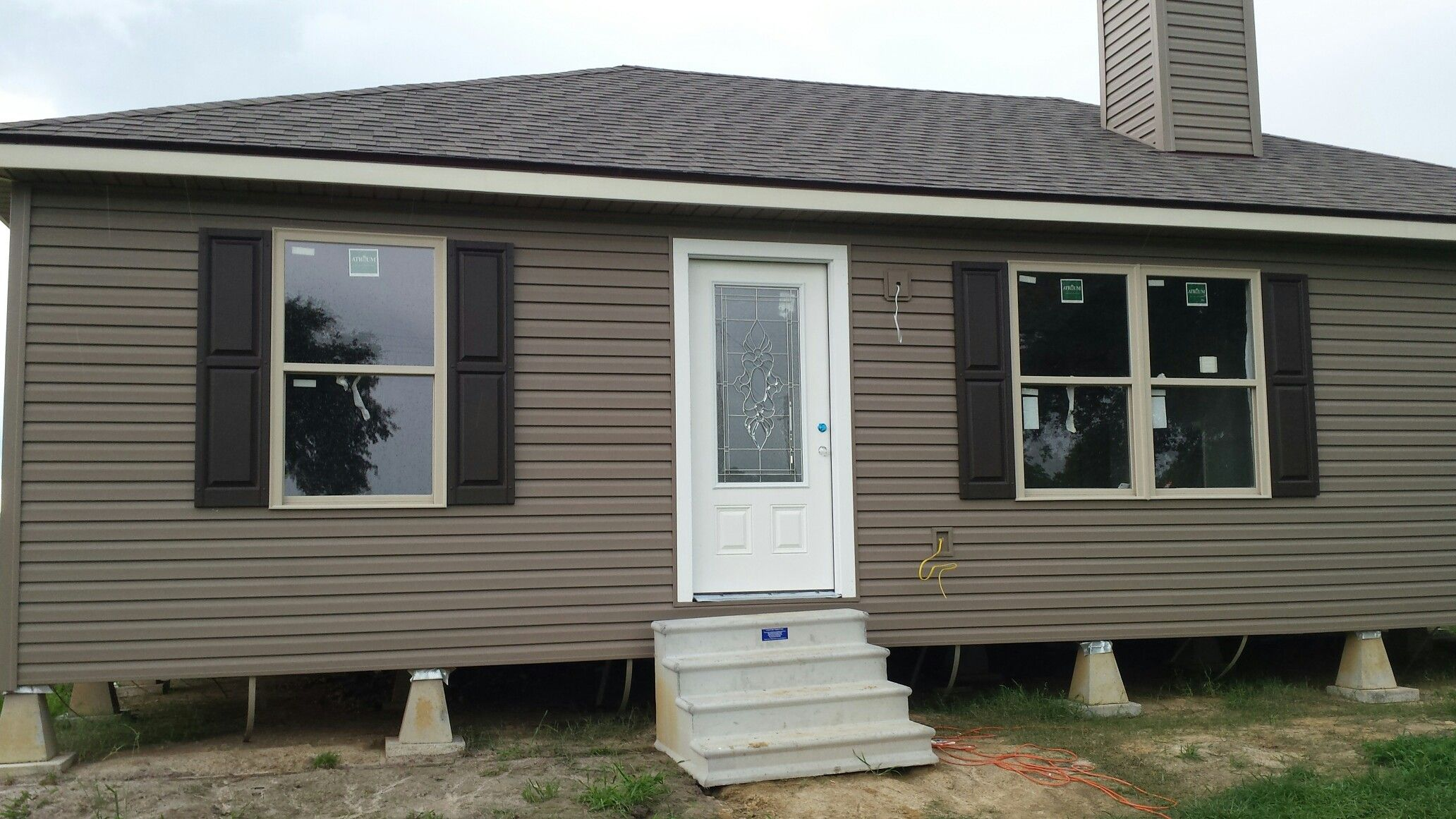 Briarwood Vinyl Siding With Almond Windows And Winchester Brown Shutters House Paint Color Combination House Exterior Vinyl Siding