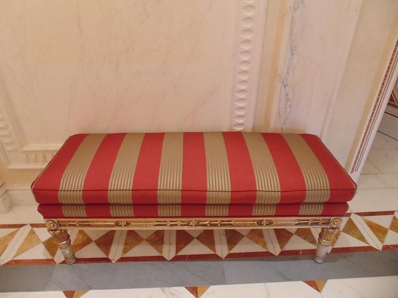 Lot 296 - Italian Neoclassical style carved and gilt wood upholstered window bench leaf and ribbon carved