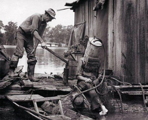"""photosofthehistoryandwithhstory:  """" A Mississippi River pearl diver, using a car's old gas tank for a helmet, prepares to descend into the river.  """""""