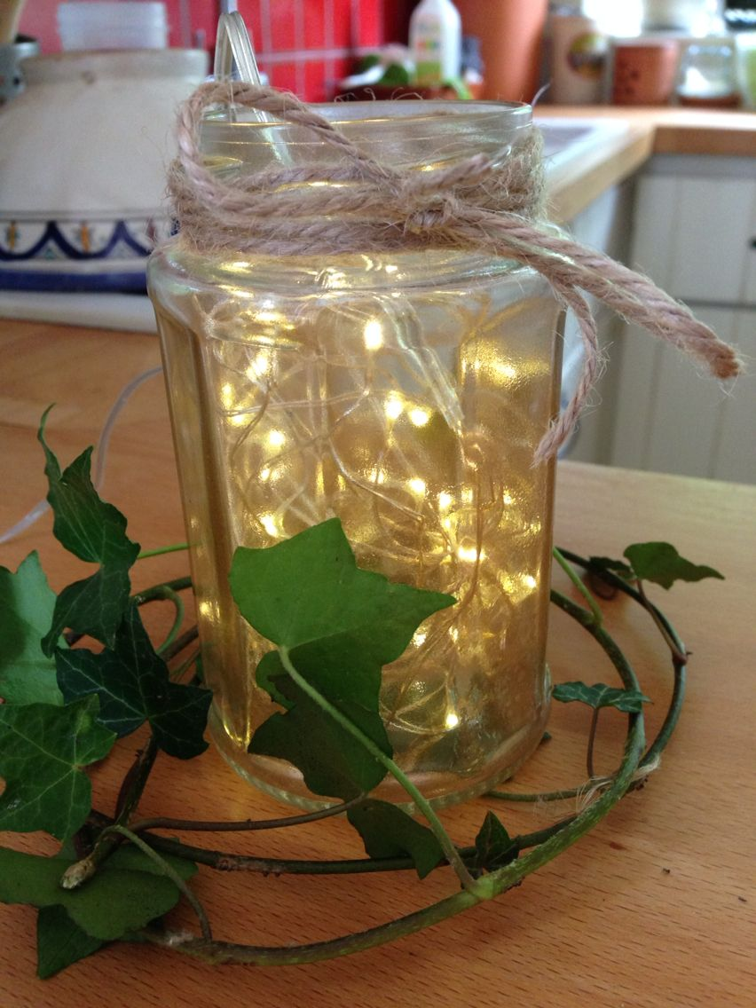 Jam jar sprayed with gold metallic paint, used as fairy light feature with fresh ivy