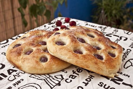 """Coca amb cireres"" is a pastry with cherries typically made and consumed in Catalonia (recipe in Catalan, translator on sidebar)"