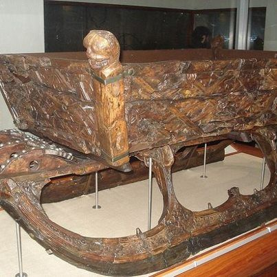 """Viking sled """"After some years as a sea-going vessel the Oseberg ship was finally laid to rest as a grave ship for a wealthy woman of high ranking. This woman received grace gifts for her journey to the realm of the dead, which included three highly decorated sleds and one sled of a simpler design (not displayed). The three highly decorated sleds were constructed in the same way: a separate upper frame was originally tied to the chassis with rope. The corner posts, shaped as animal heads"""