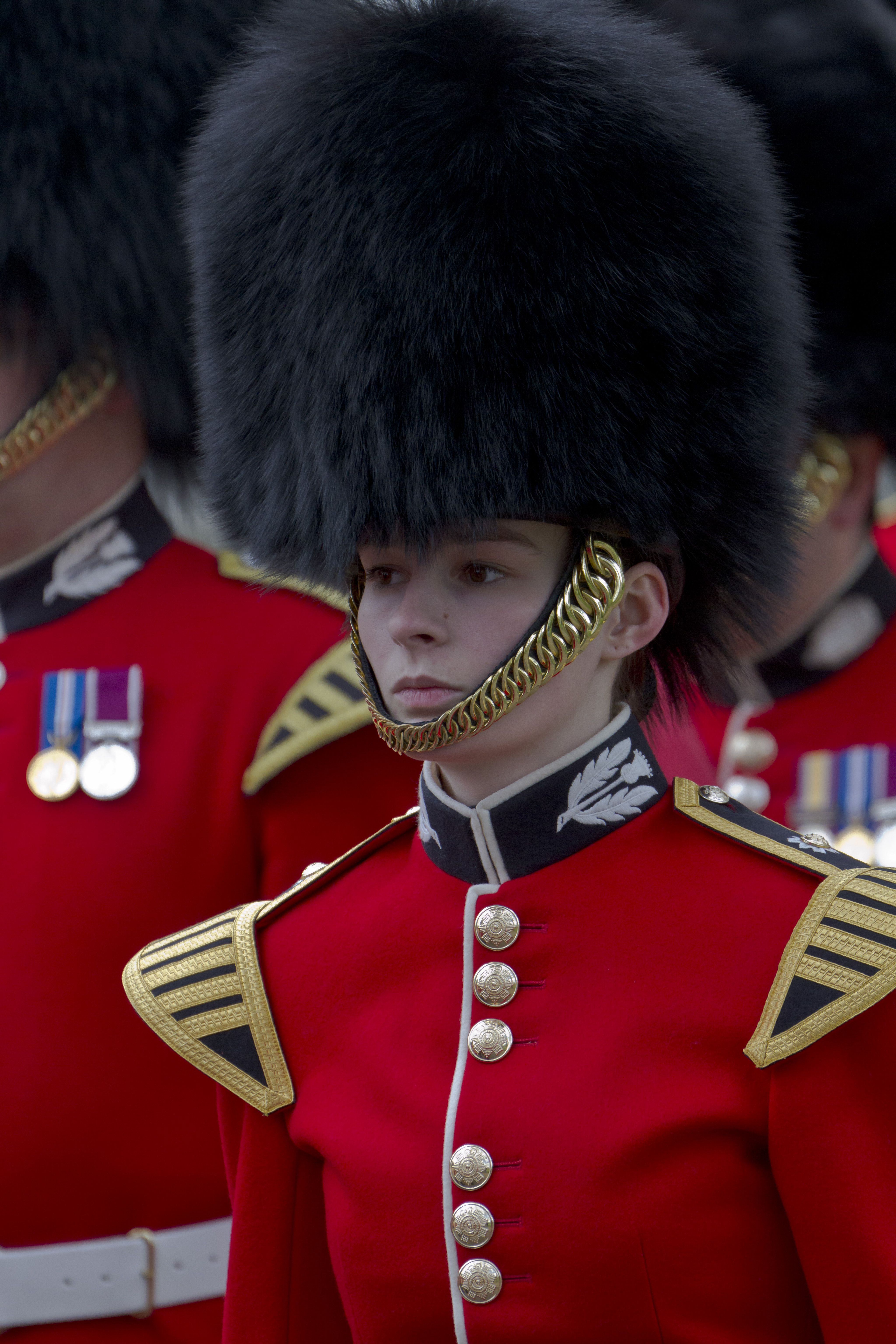 This bandswoman of the British Army s famous Scots Guards proudly wears her bearskin  hat well  and if you mistakenly call it a