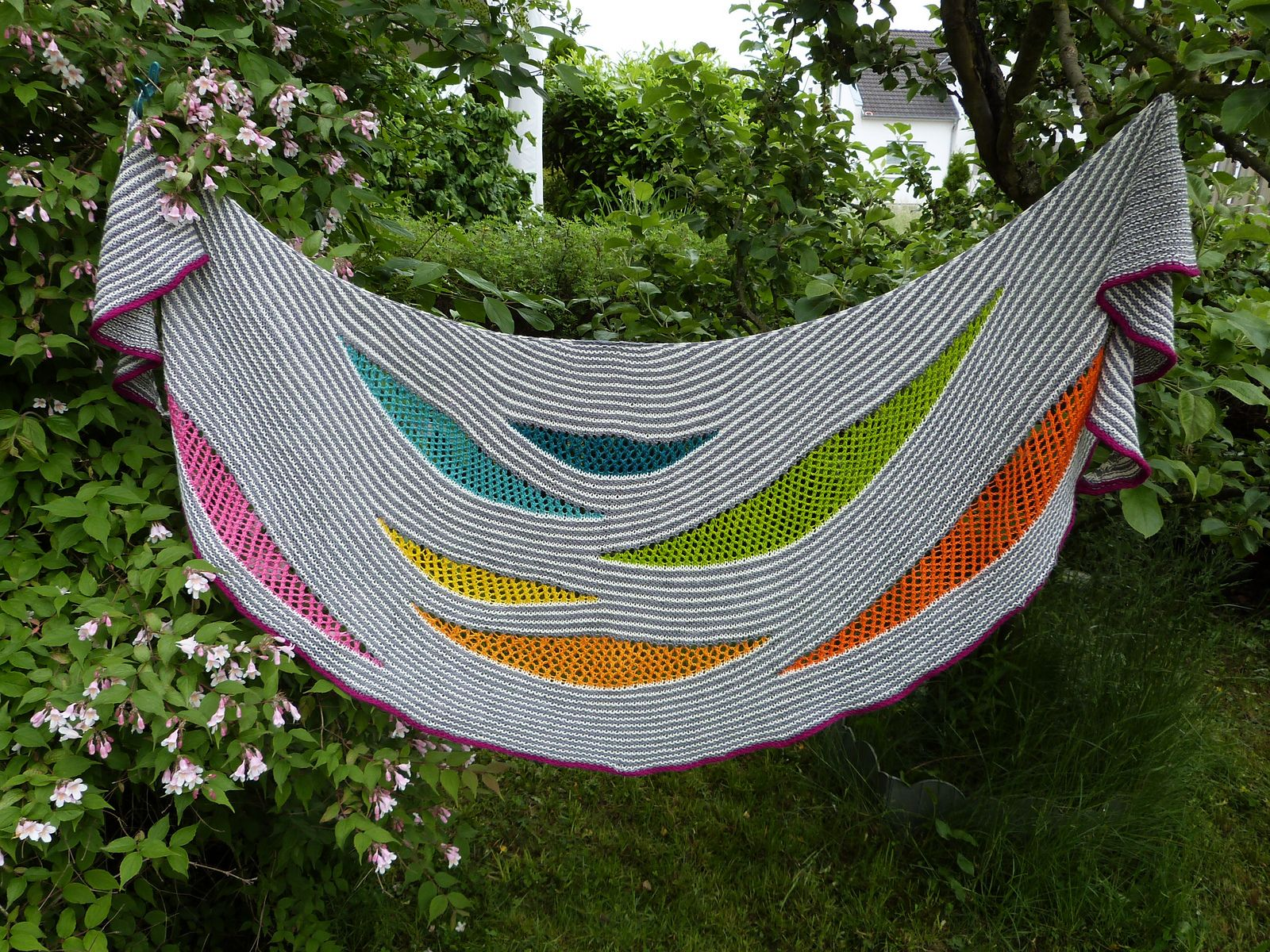 My Summer Song is a fun to knit crescent shaped shawl worked in garter stripes, which open up in various spots to play with different lace and multiple coloured crescent inserts.