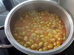 HABAS A LA CAZUELA CON JAMÓN  Ingredientes (5 personas): 1,50 kg. habas frescas 2 dl. de aceite de oliva 1 cebolla 4 dientes de ajo 1 cucharada pequeña de pimentón dulce 1 cuchara de vinagre 2 cucharadas de pan rallado 1 dl. de caldo  Elaboración: Se pican las habas finamente y se lavan. Se ponen a escurrir, y a continuación en una cacerola se pone el aceite. Cuando esté caliente se echa la cebolla y el ajo muy picado y cuando esté rehogado se le añade las habas, los aliños, el caldo y el