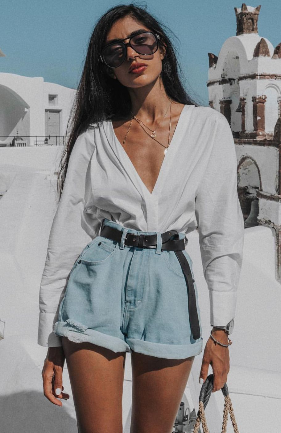 vintage feel boyfriend light denim high waisted short rolled up at the hem matched with a dark brown leather belt and crisp white long sleeve blouse is perfect for a day at the beach. #beachhoneymoonclothes