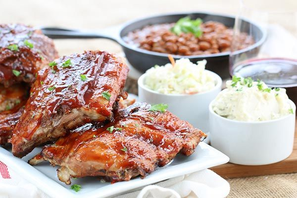 Smoky barbecued ribs on a table with cole slaw and baked beans
