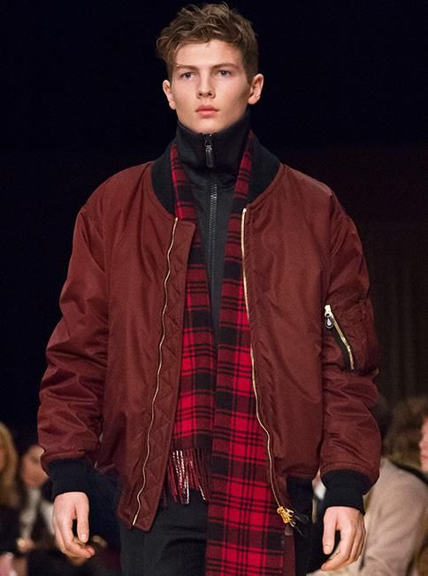 A dark red men's bomber jacket from Burberry, detailed with black knitted collar, hem and cuffs and worn with a tracksuit jacket and check scarf