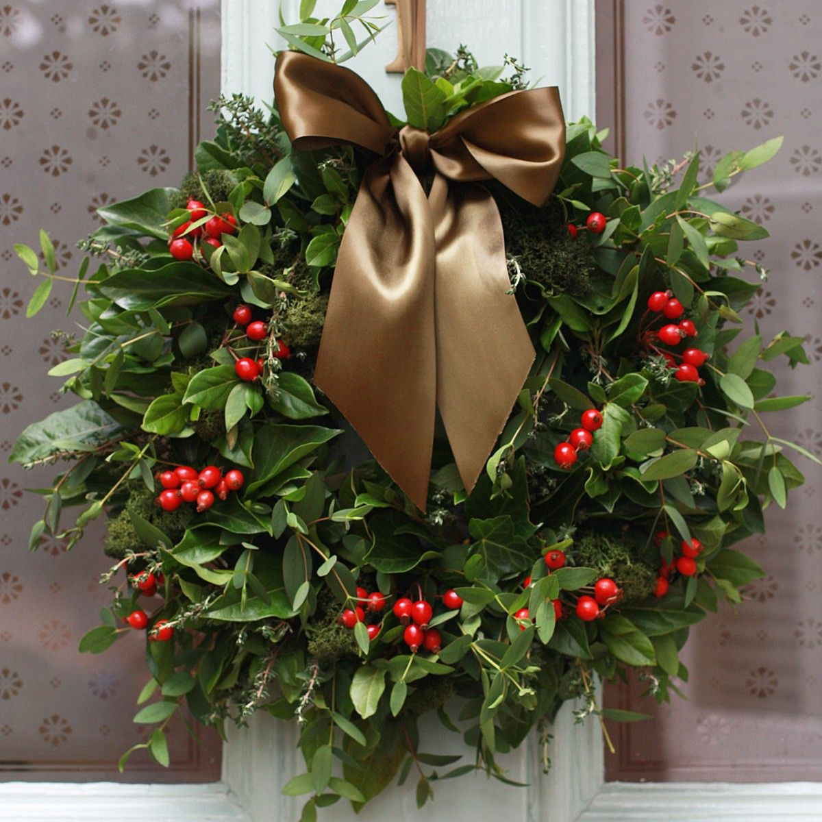 Front door christmas wreaths - Beautiful Natural Christmas Wreath Composed Of Green Leaves And Red Berries With A Large Brown Ribbon