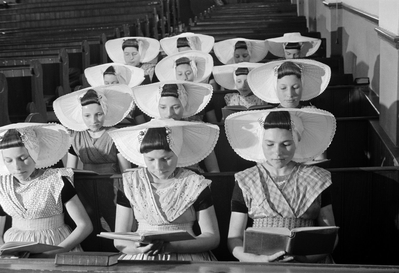Girls in traditional costume visiting a church, Arnemuiden (ca. 1942)  photo: Heemskerck Düker, W.F.